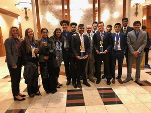 12 BHS DECA students and their 2 advisors pose with the trophies they earned at Districts.