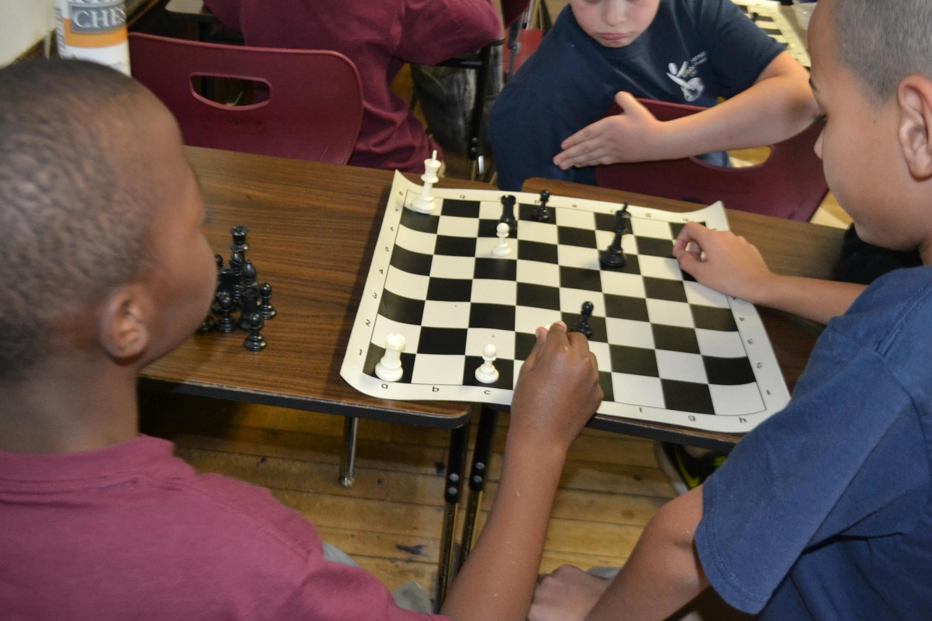Students gathered around to play a game of chess