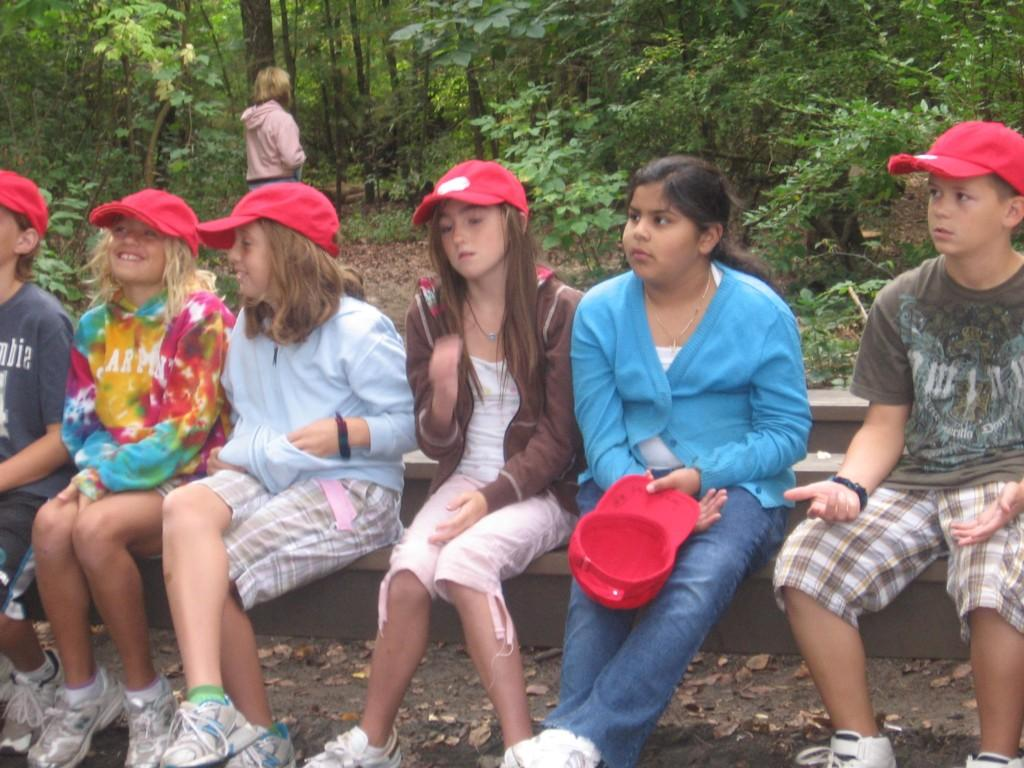 kids sit quietly outside at camp