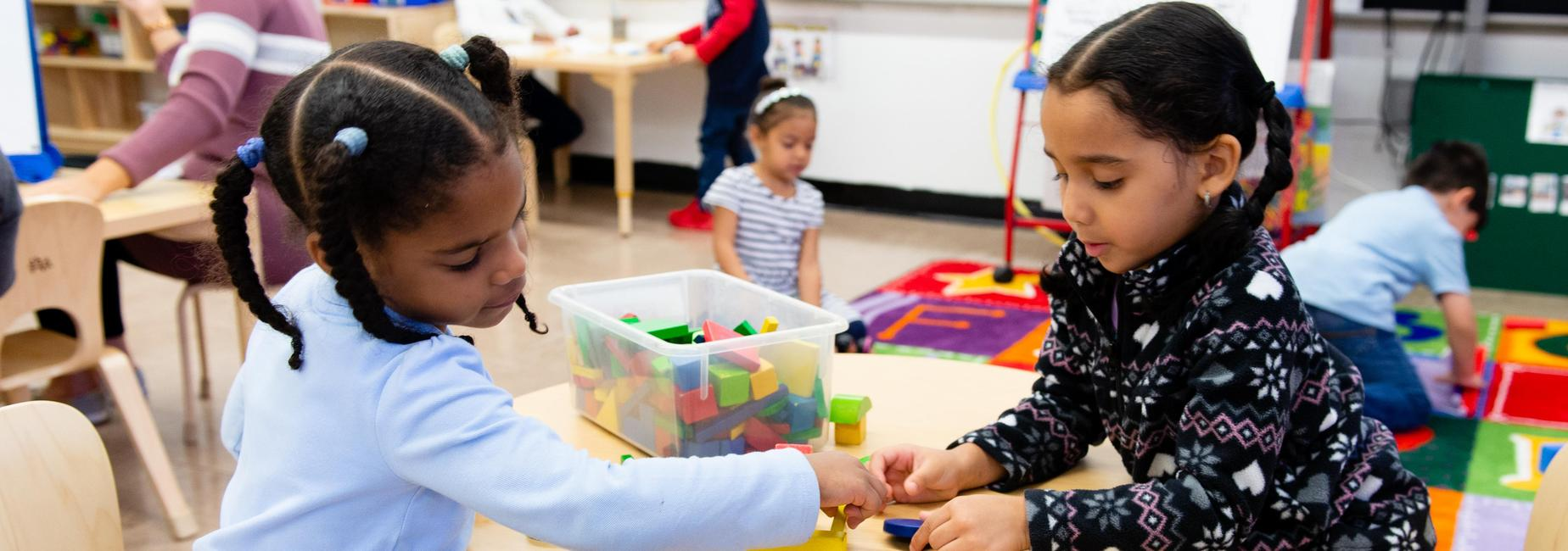 Two pre-k students playing with blocks at a table.
