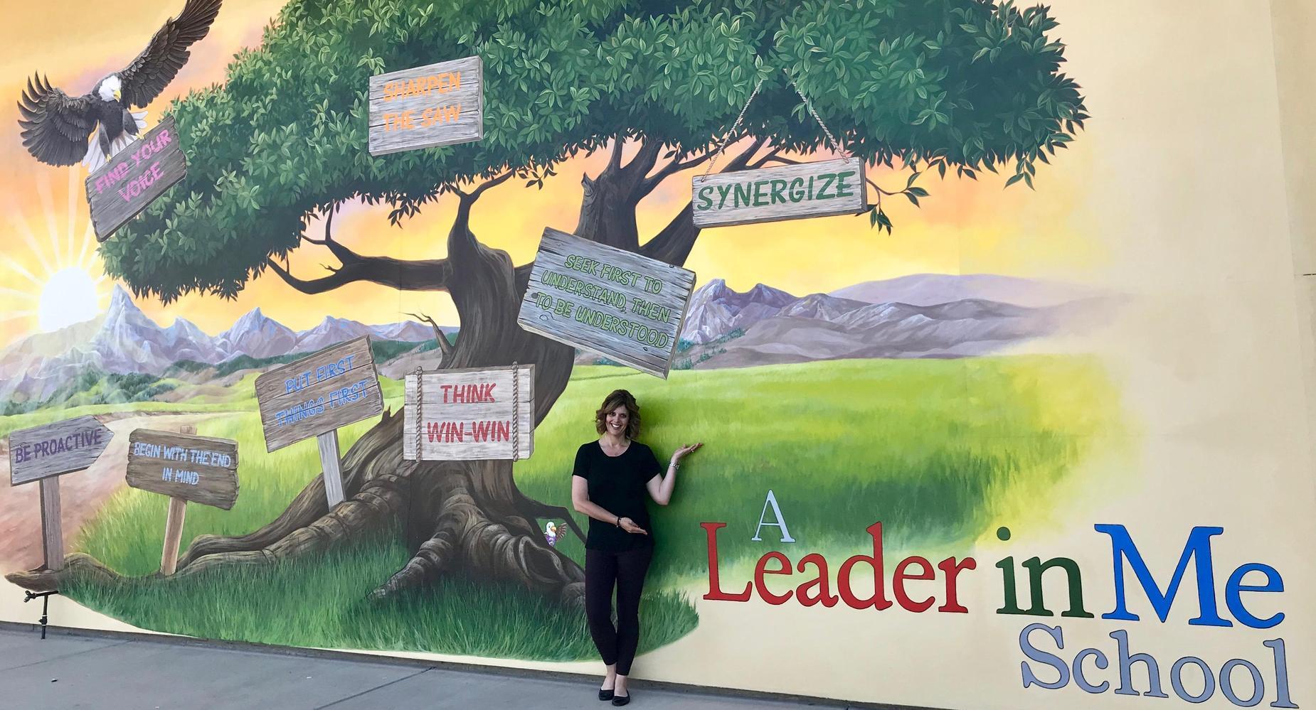 School Principal standing by school mural showcasing Leader in Me