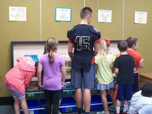 East Davidson football player is choosing books with students.