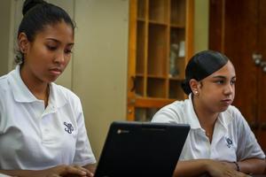 Girl sits behind laptop