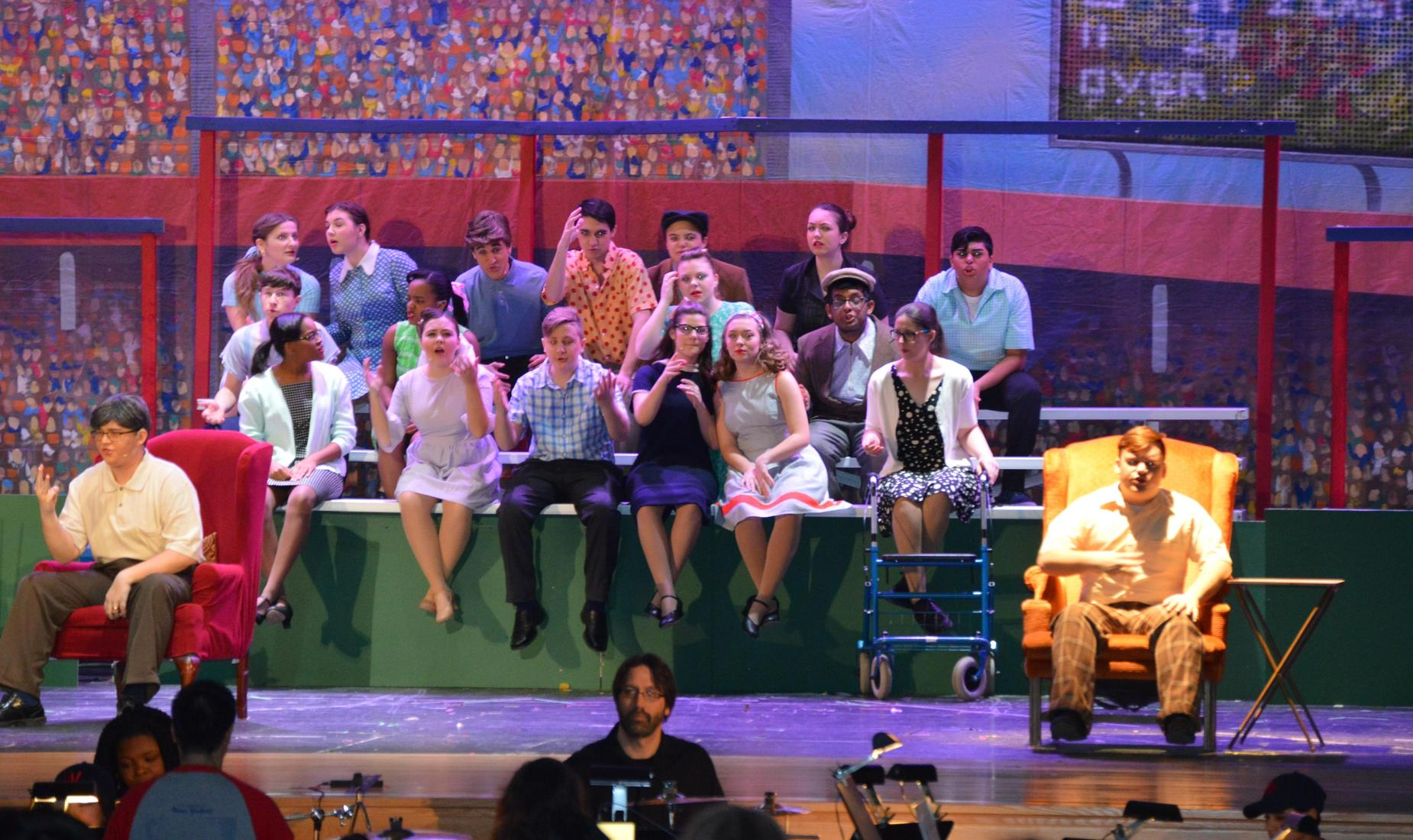 19 BHS drama club students perform Damn Yankees. They are sitting on bleachers with 2 sitting on chairs. The background looks like a baseball stadium with fans in the stands.