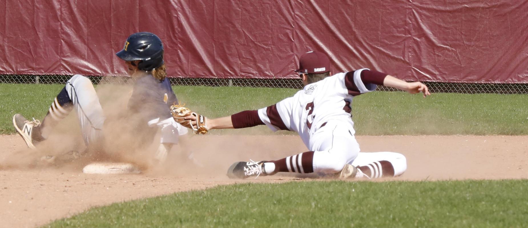 baseball player in white uniform touches boy in blue uniform with baseball mitt