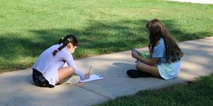 Photo of two students doing schoolwork while sitting outside on sidewalk