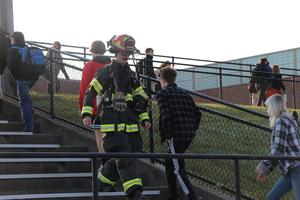 A firefighter walks past students during the stair climb event.