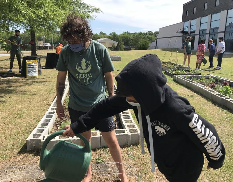 USC volunteer Louis Rubino works with a PRMS student on watering plants