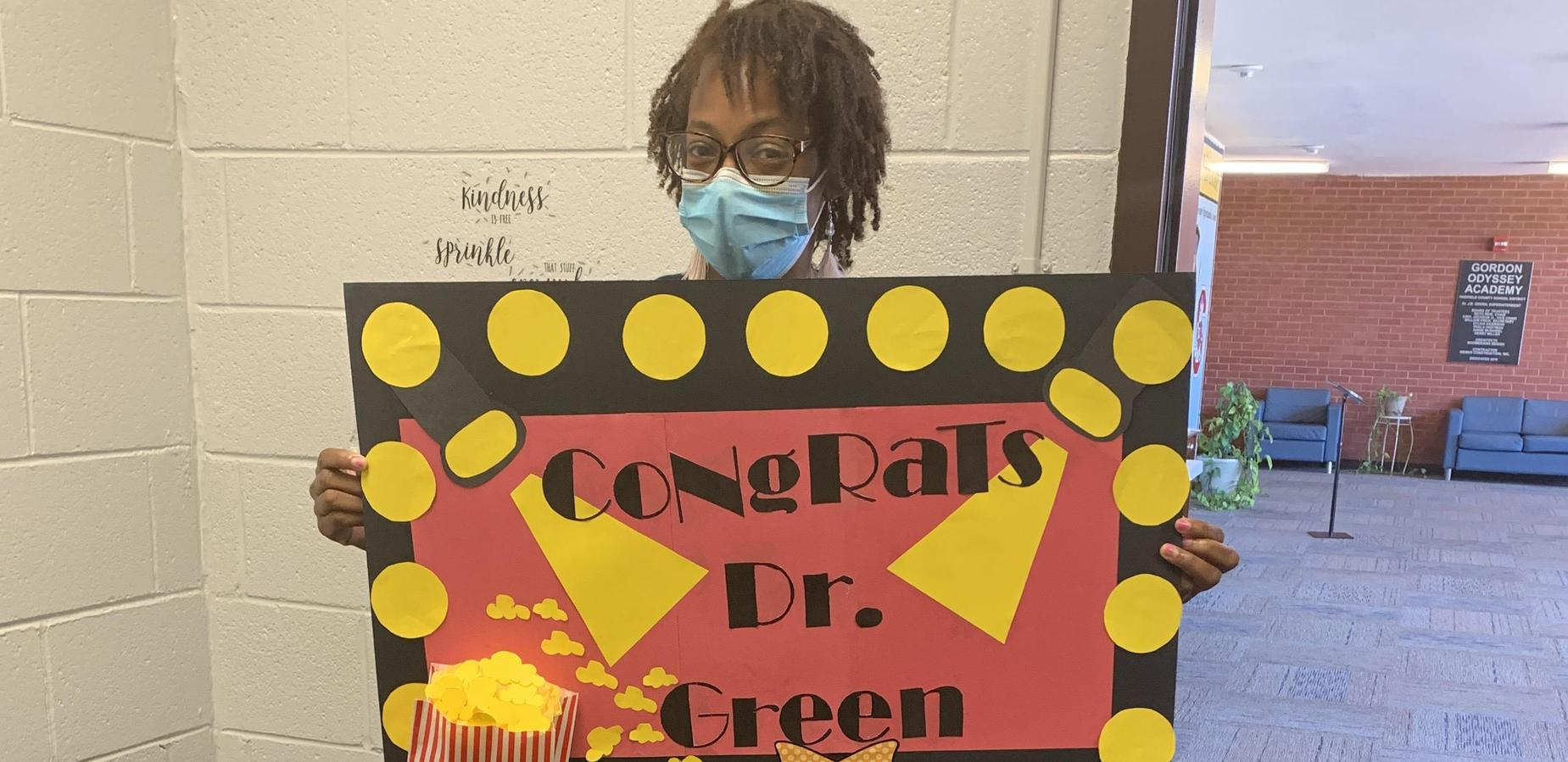 Ms. Guinyard holding her creative poster honor Dr. Green
