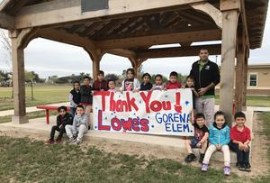 Gorena Elementary School students pose for a photo underneath their new pavilion with their kindergarten teacher, Norberto Ramos.