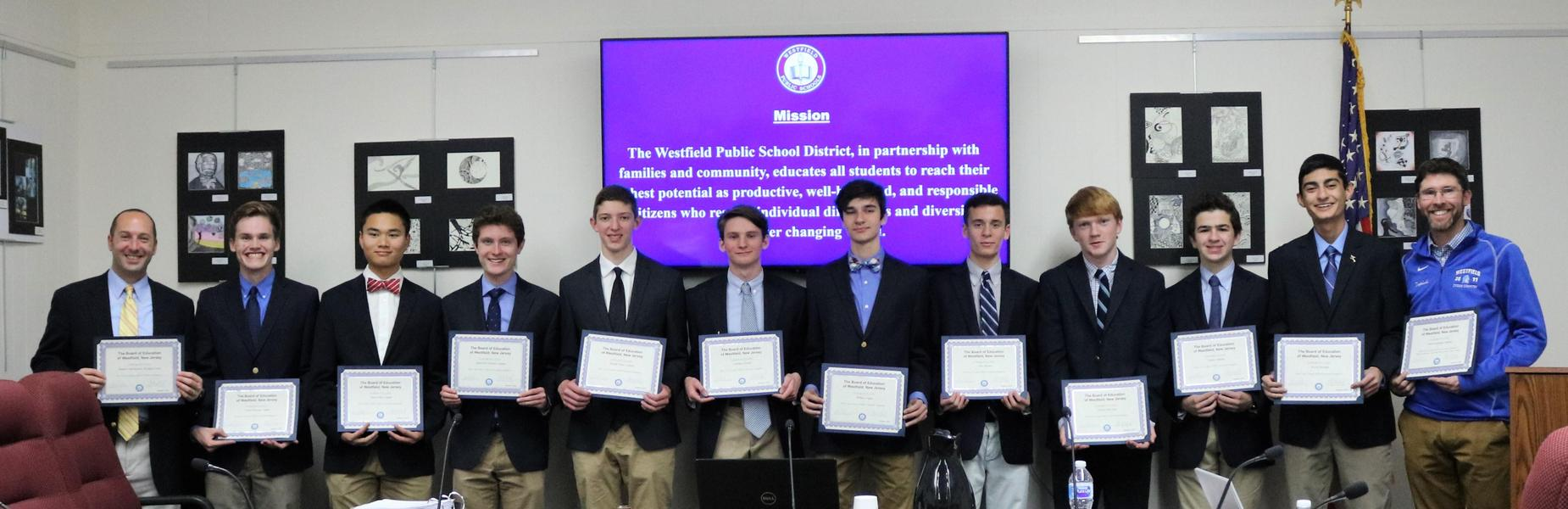Westfield High School Boys Cross Country Team and their coaches are recognized at Dec 4 Board meeting as sectional champions.  Here, ten of the runners, including 4 captains, are flanked by their two coaches as they pose for the picture holding certificates.