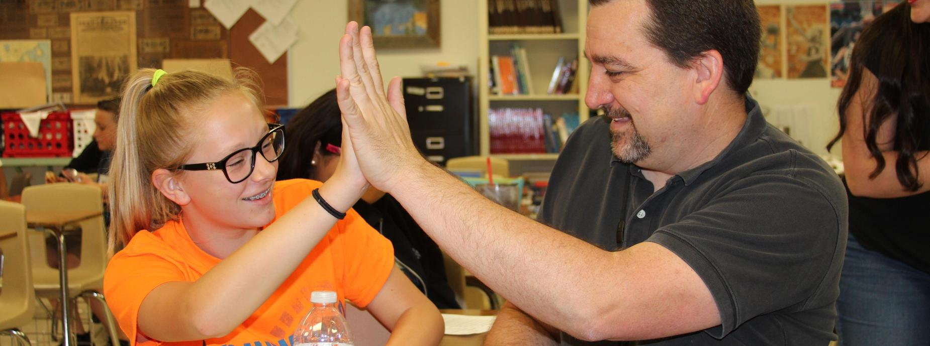 Student giving teacher high-five