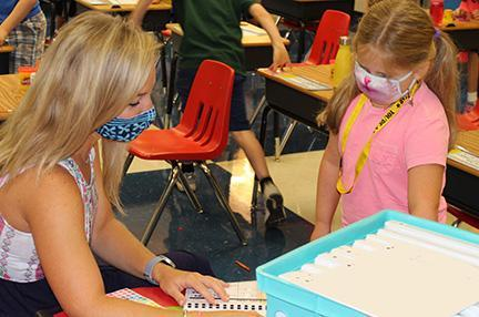 Mrs. Owen works with a student.