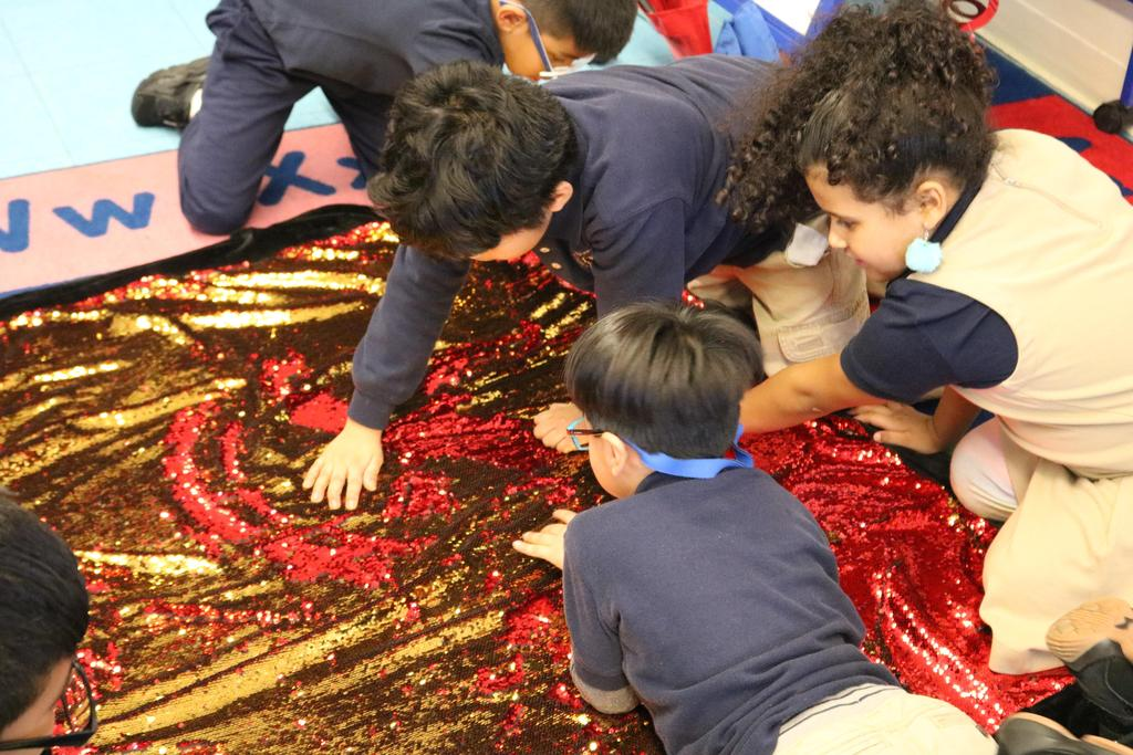 kids feeling a beaded blanket