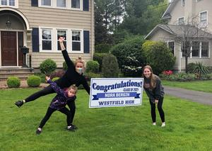 Photo of WHS 12th grader posing with teacher and child with lawn sign