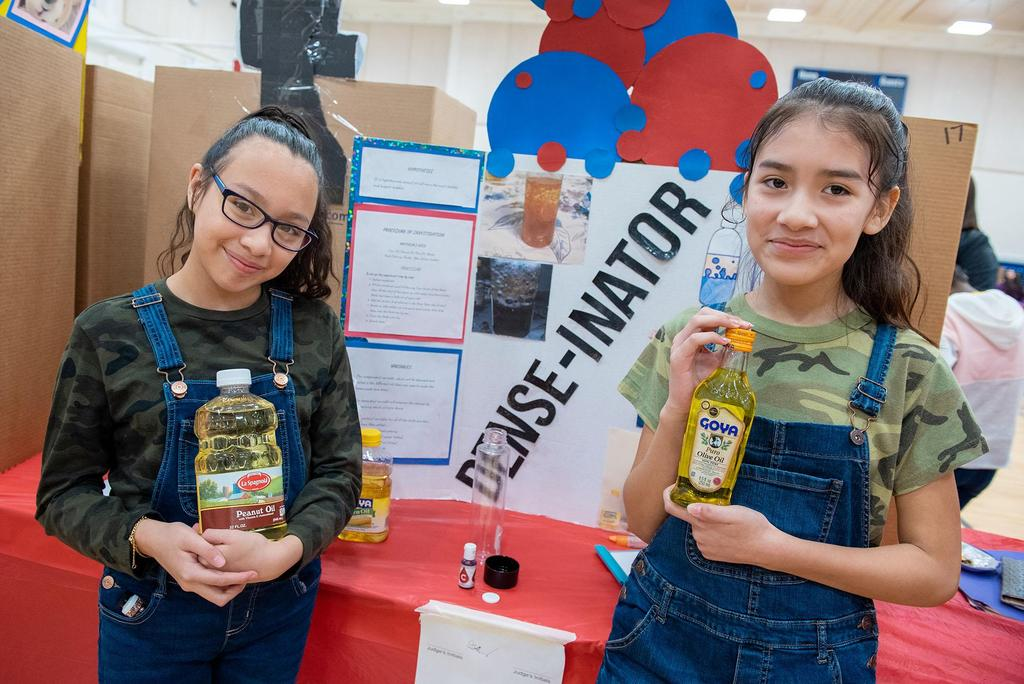 Two students in front of their project, each holding a different container of oil