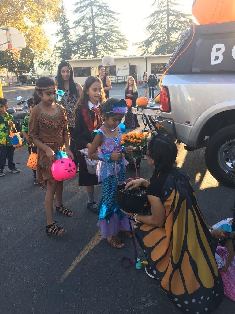 Person dressed as Butterfly handing out candu at Trunk or Treat