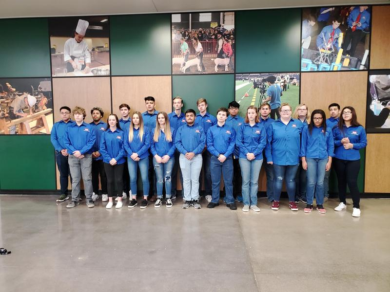 group of 20 students pose together in matching shirts