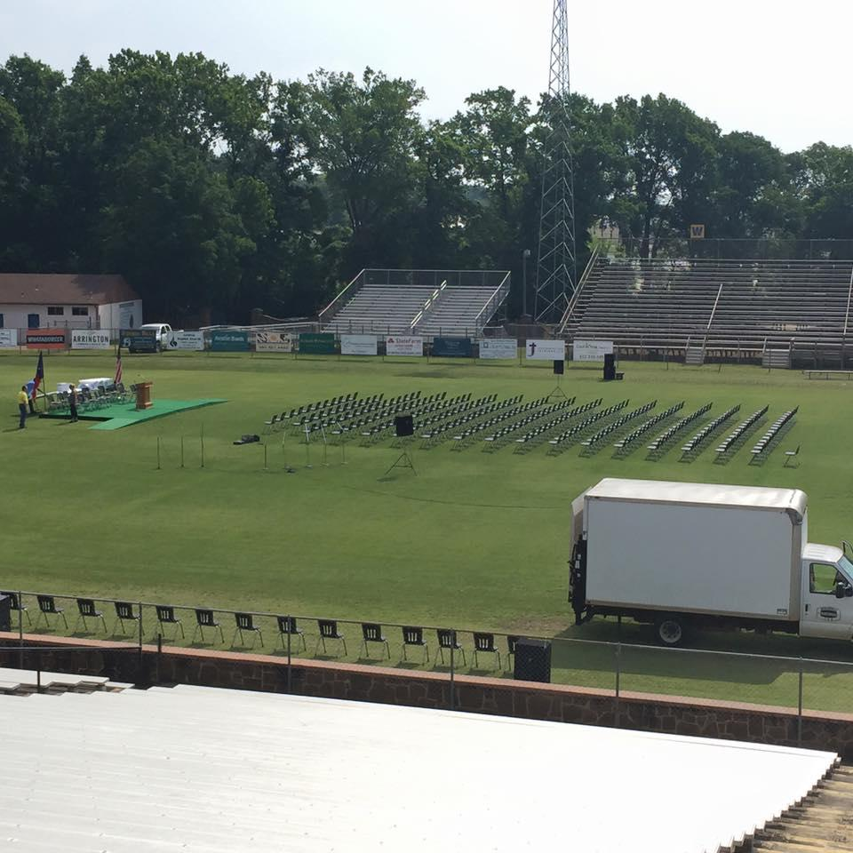 field set up with chairs and stage for graduation