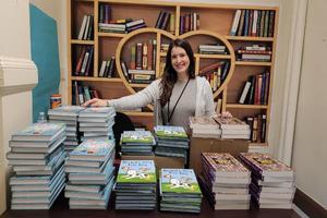 Ms. Fernandez behind stacks of new books