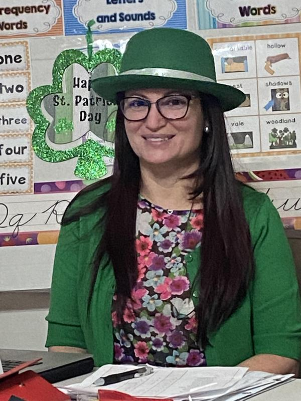 Mrs. Almeida wearing green at her desk
