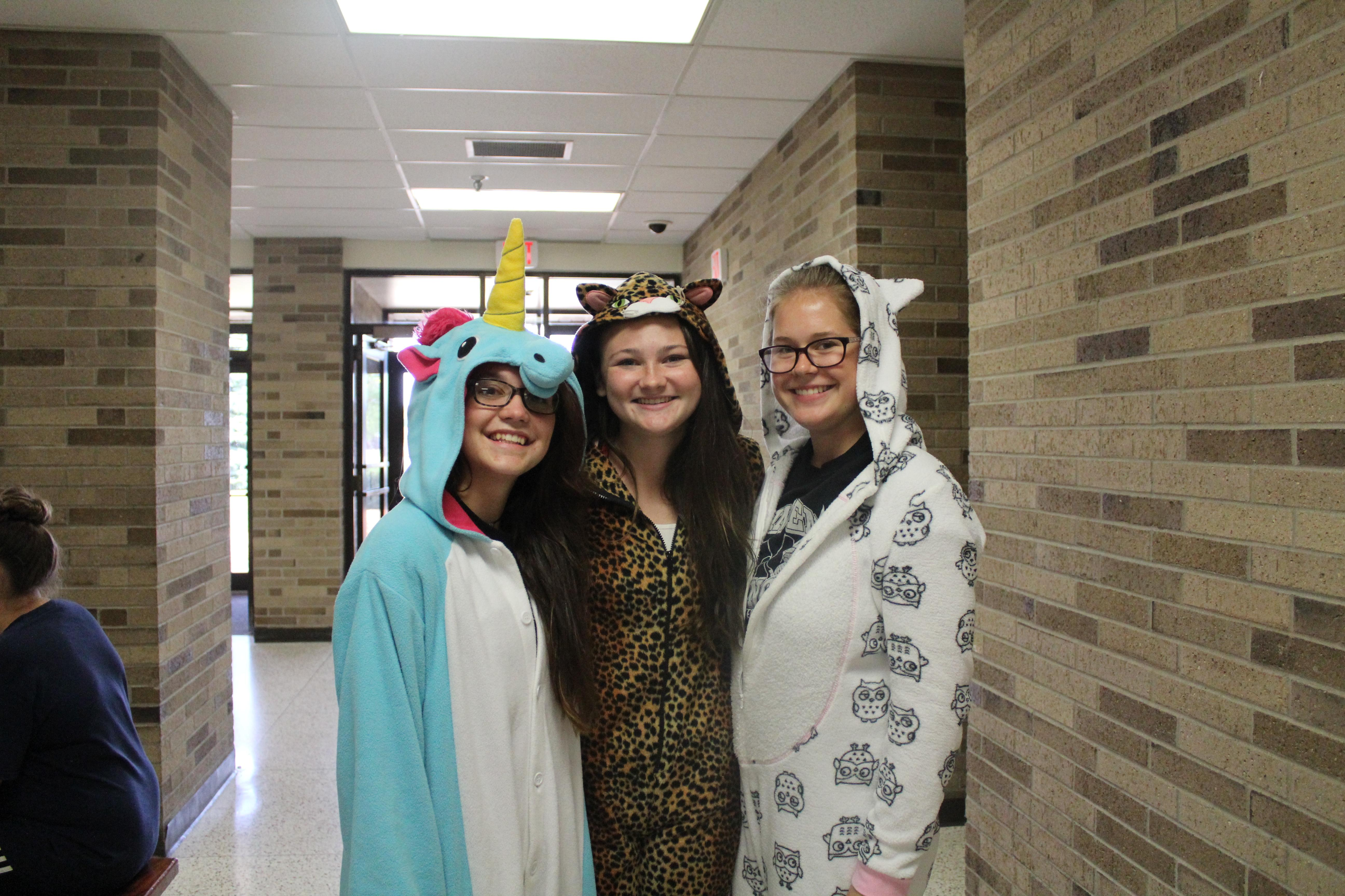 Three students in pajama costumes with hoods.