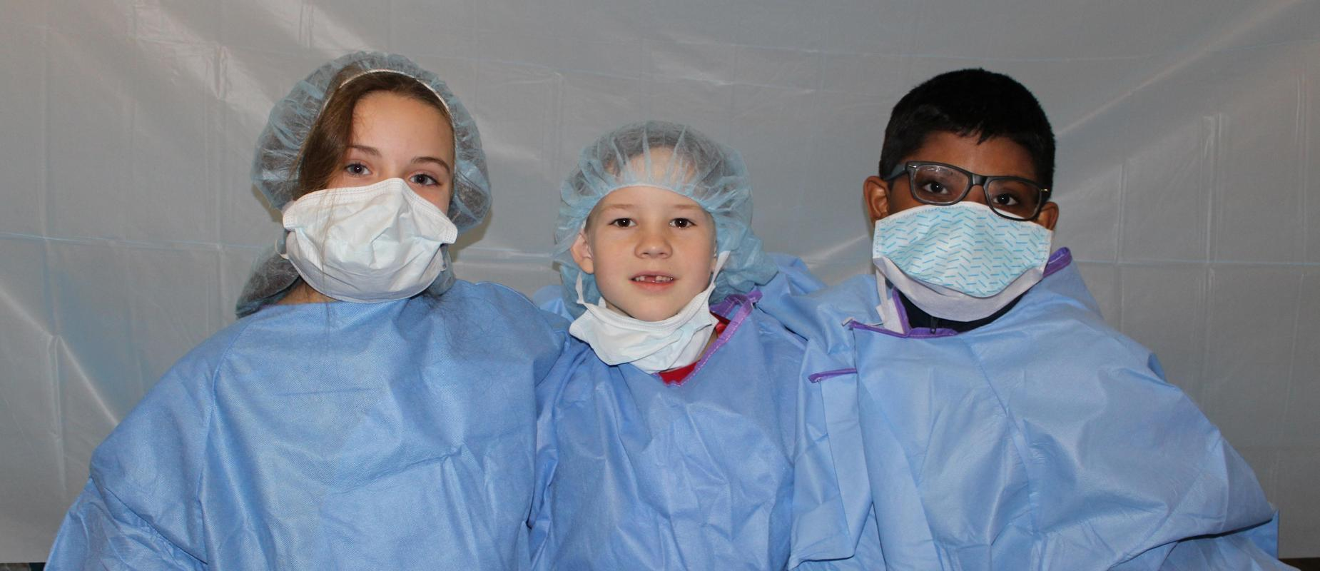 three third graders in hospital scrubs and masks