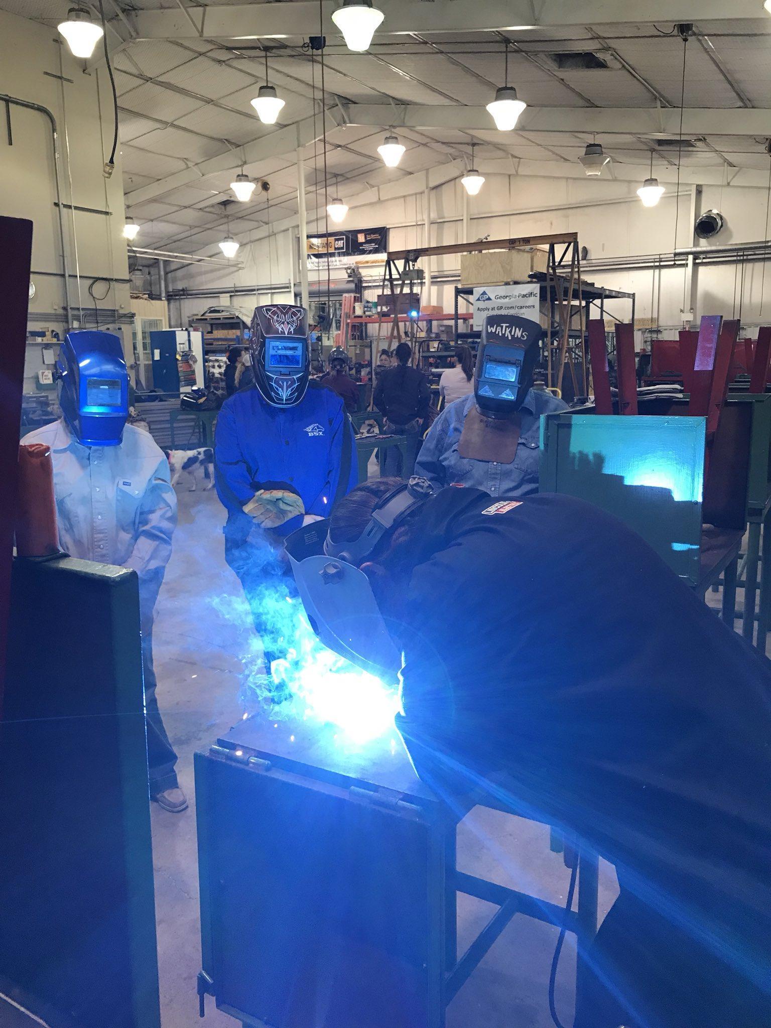 students welding wearing protective face helmet