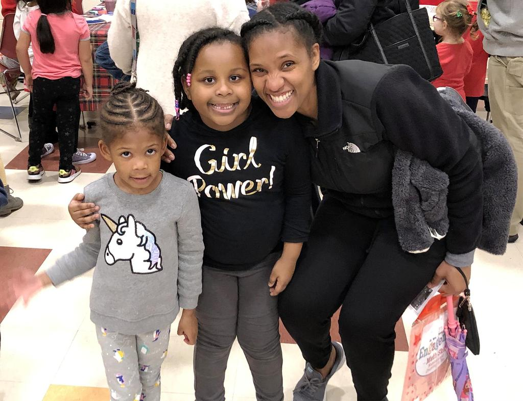A woman and two young girls smile for the camera