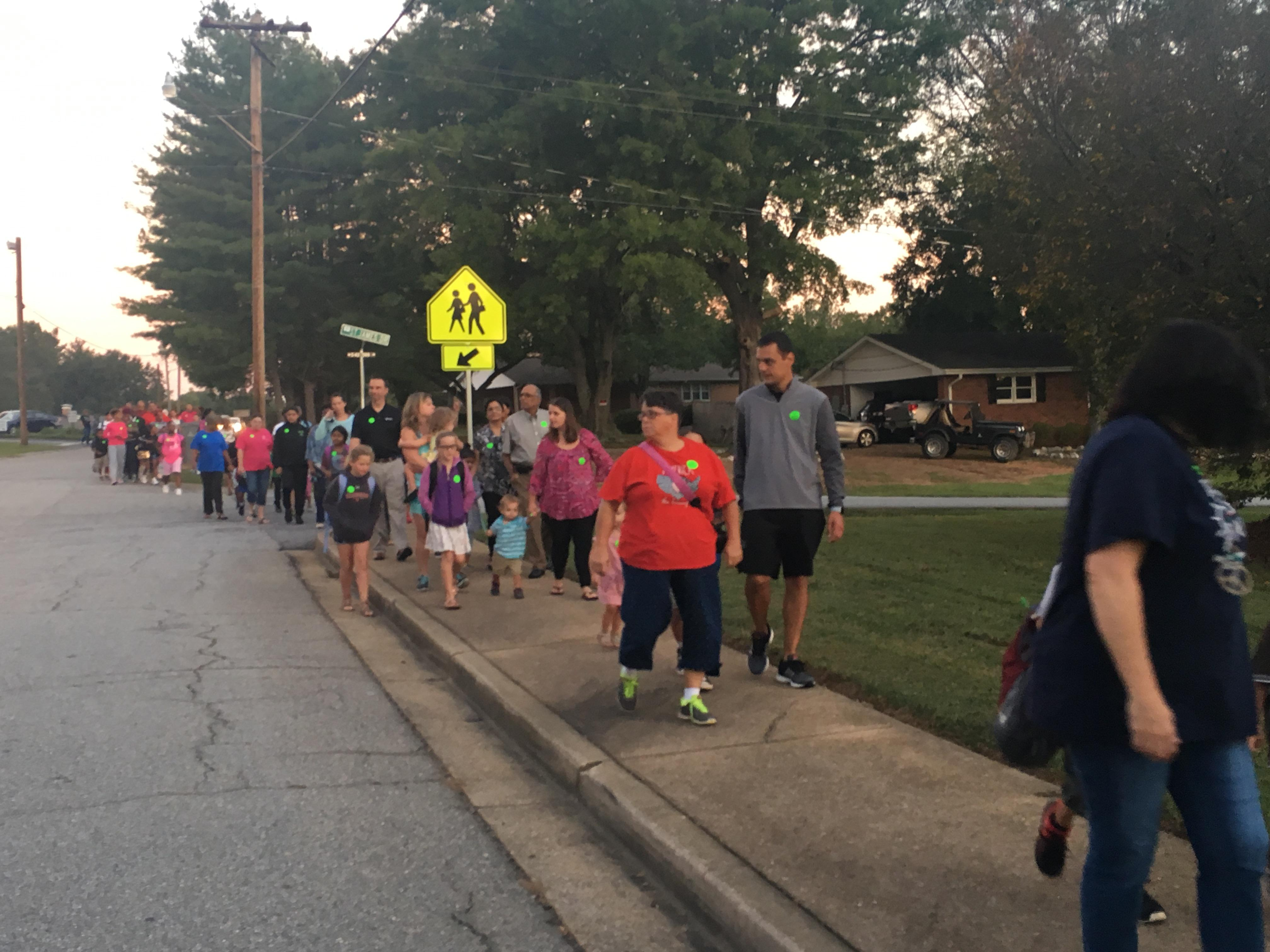 Family members walk to school with their children