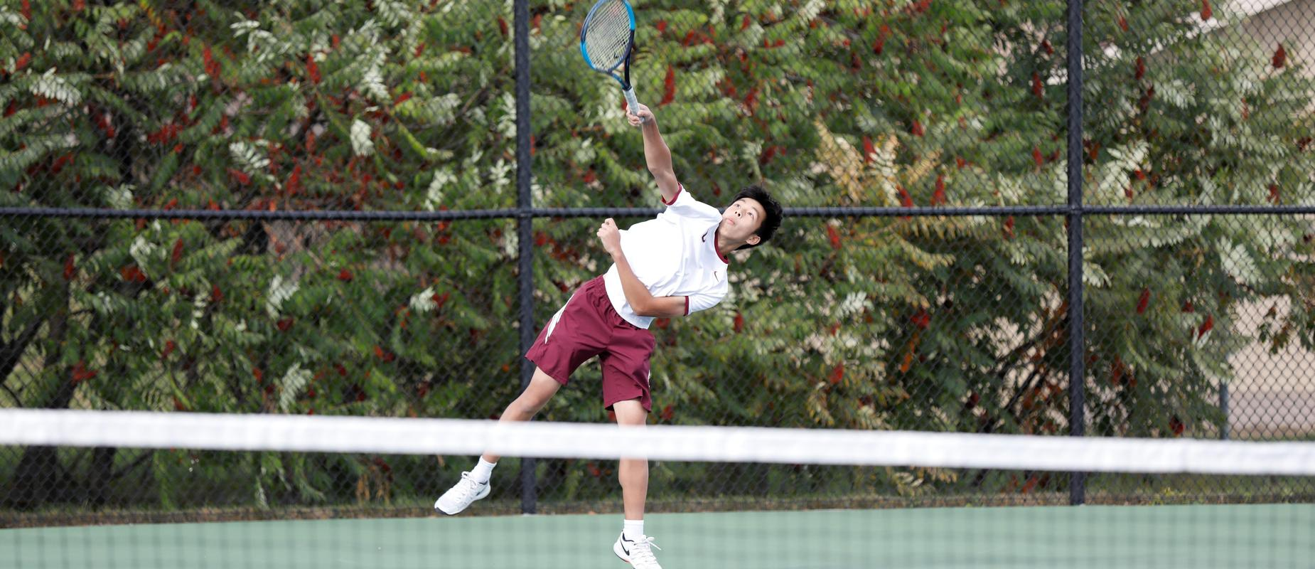 varsity tennis player on court with bushes behind fence
