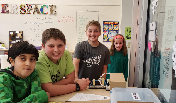Boys and girls pose with a smile in Makerspace.