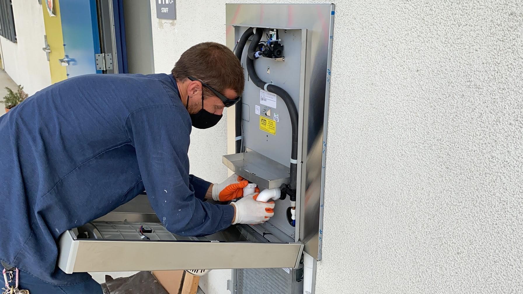 EMCSD Floor Care team member, Travis Kerr, installs new bottle filling station.