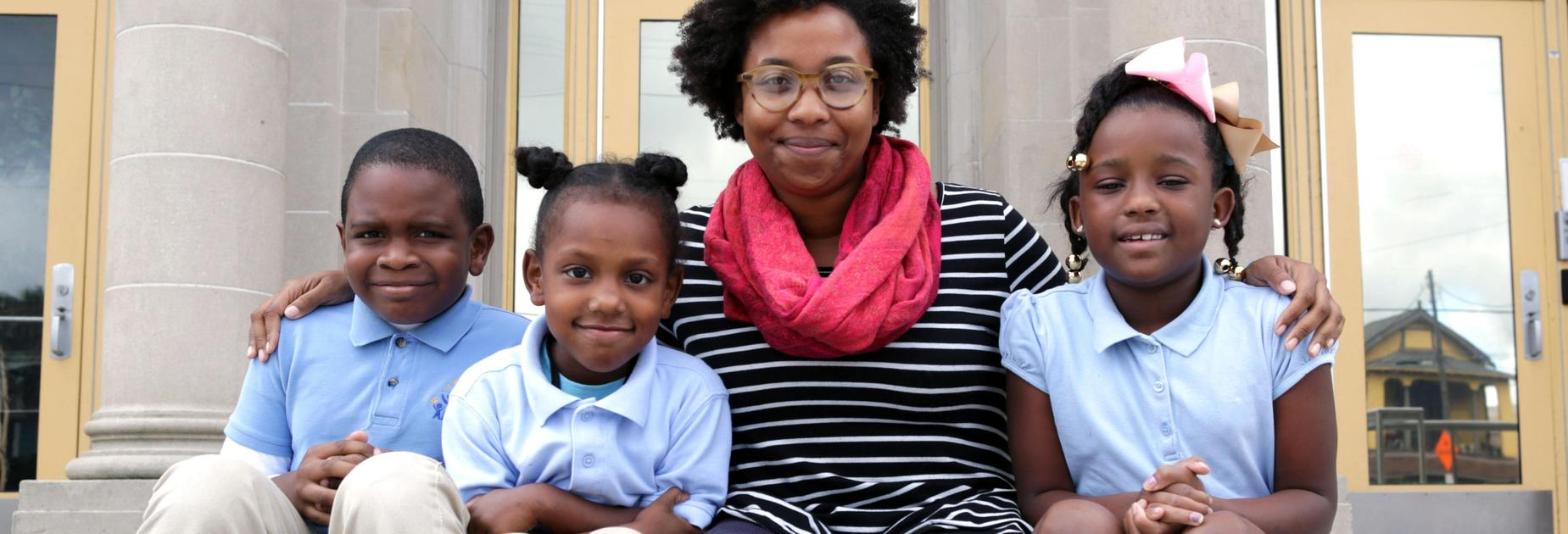 Three KLP students sit on the steps to the school with the principal