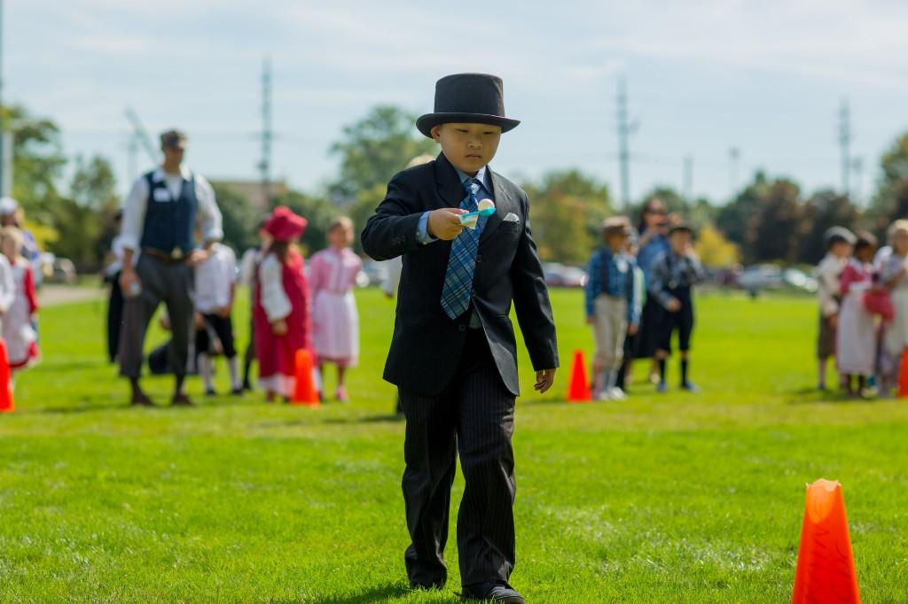 Boy in top hat playing egg race