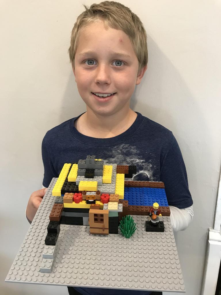 boy holding lego house he built