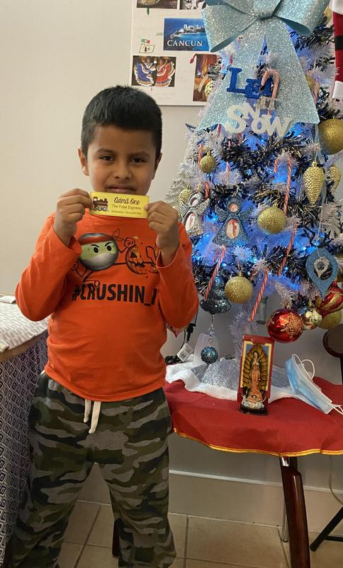 Edwin holding ticket in front of Christmas tree