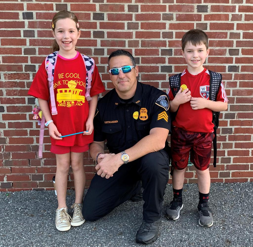 Photo of Westfield police officer with two students on Walk to School Day.