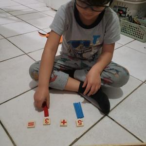 boy doing math activity with sticks and tiles