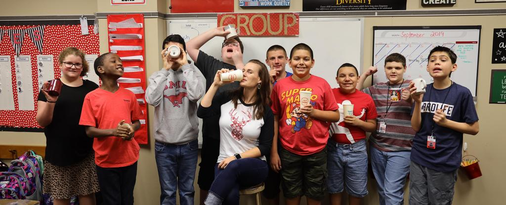 students posing with coffee cups