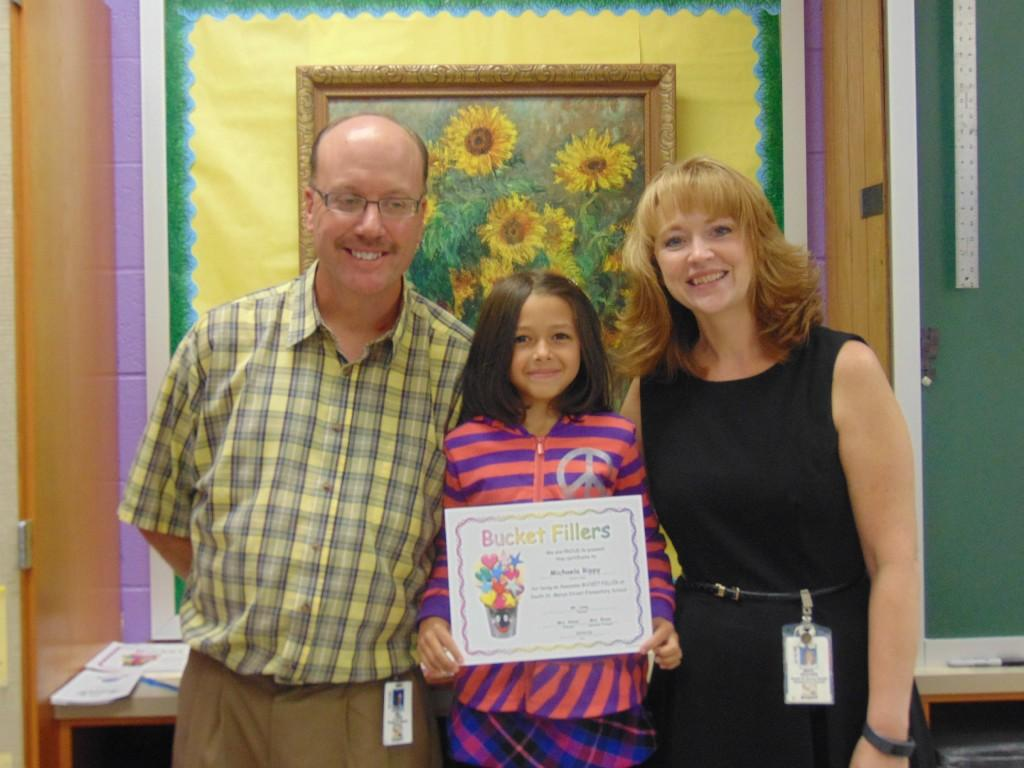 Image of student of the month with teacher and principal