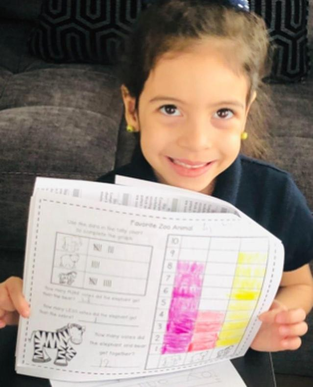 smiling girl showing off her math activity sheet