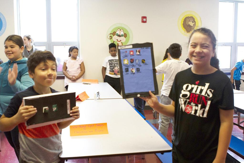 Students hold up their STEM projects