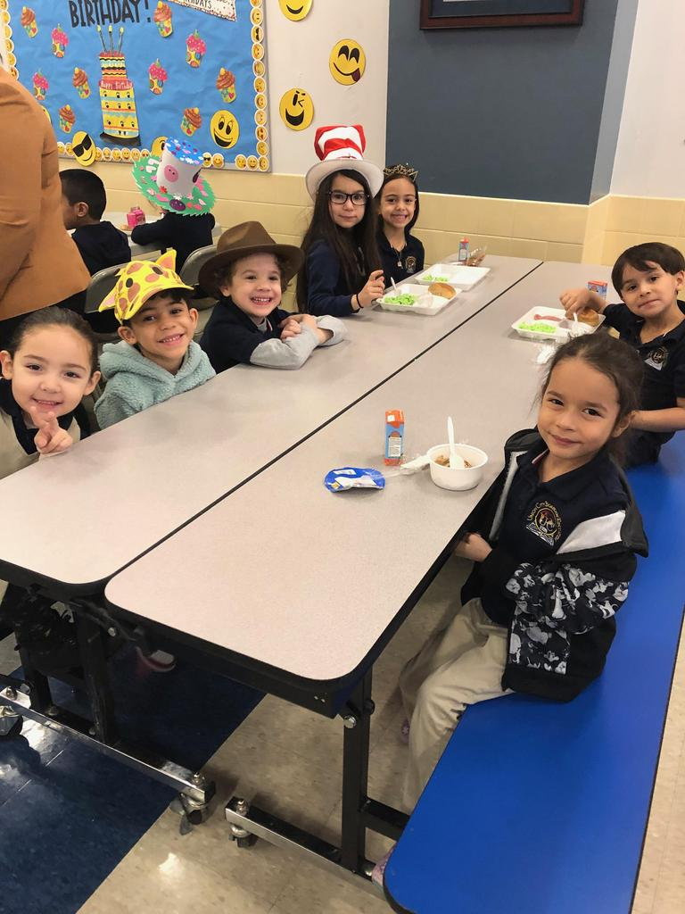 group of children enjoying breakfast wearing wacky hats