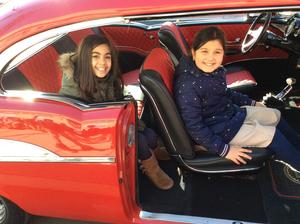 two girls sitting inside of the 57 Chevy