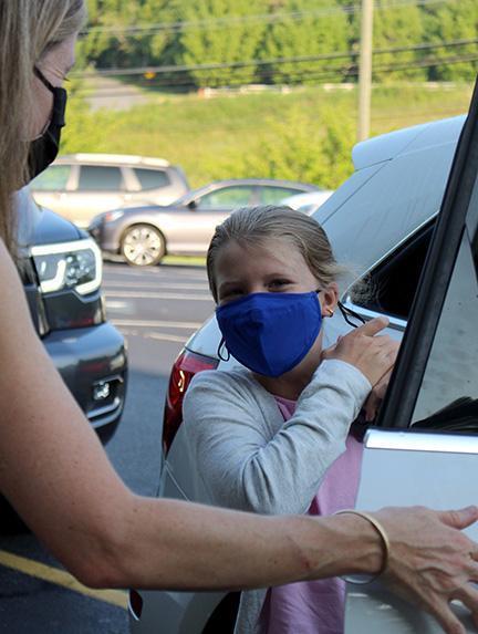 Student exits car during morning carpool.