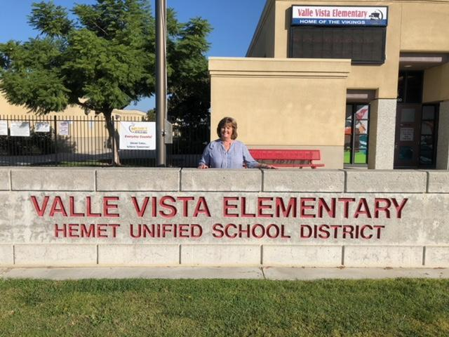 Kathleen Clark standing behind a Valle Vista sign.