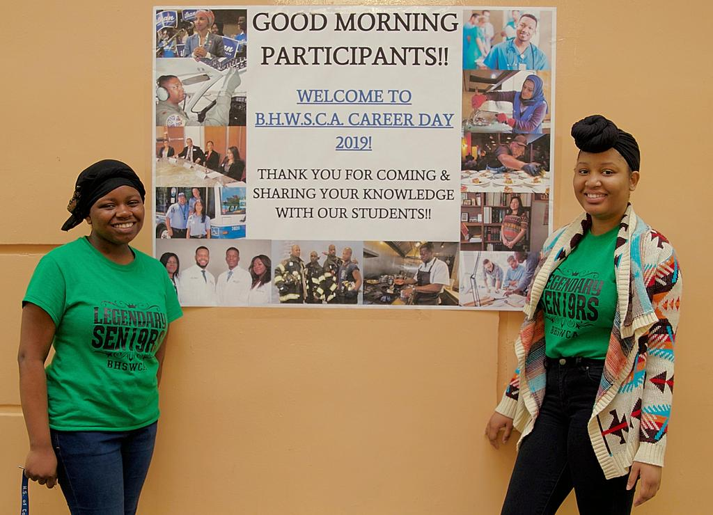 Two students smiling with a career day poster