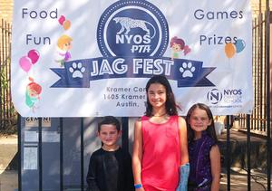 One boy and two girls standing in front of a Jag Fest banner.