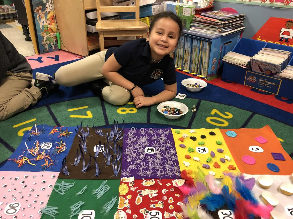 little girl smiling in front of the 100 days of school banner